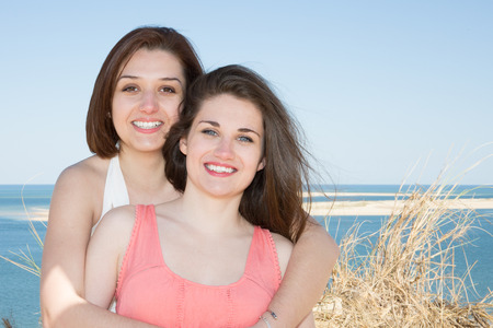 Happy lesbian couple girls taking selfie with mobile smart phone camera on beach summeer