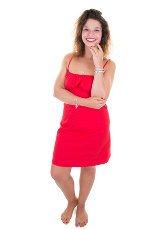 Portrait of smiling young attractive woman positive female with cheerful expression, dressed in red full length dress and barefoot