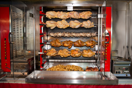 Red roasted chicken in row turning at industrial roaster at food truck in shop