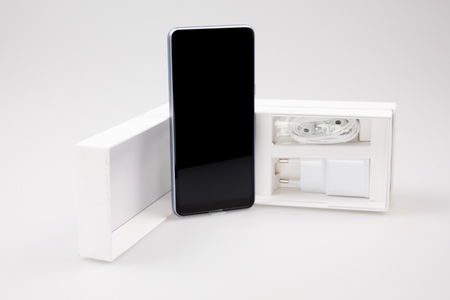 White box of new smartphone cell phone isolated on clear grey background
