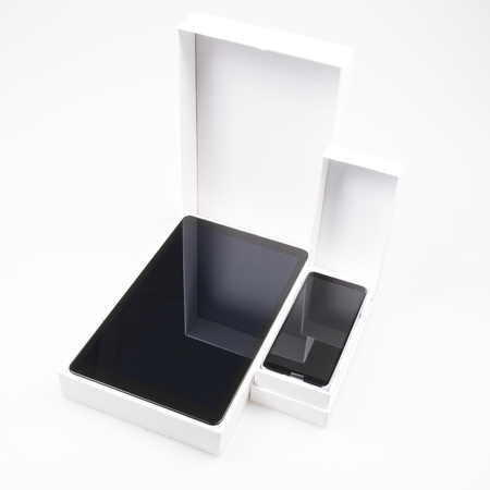New Smartphone and tablet flies out of white box package isolated on white background