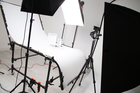 Lighting setup in studio for commercial works such as photo object product with big softbox snoot reflector umbrella and tripods Фото со стока