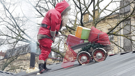 Santa Claus pushes a pram filled with gift on a roof with a smokestack Zdjęcie Seryjne