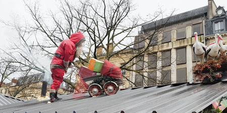Santa Claus pushes a pram filled with gift on a roof with storks