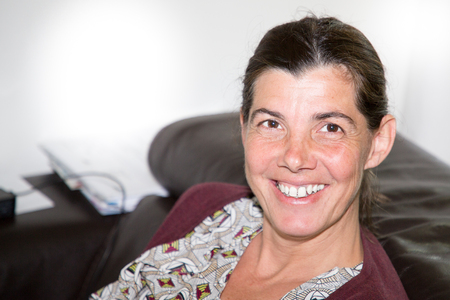 woman smiling her hair back on her couch