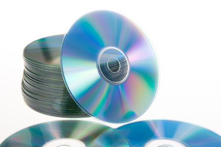 blue tinted close-up of a stack of cd-roms CD lying on white table Stock Photo - 114970172