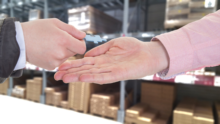 businesspeople hands exchanging a puzzle piece in a warehouse