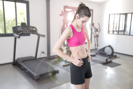 fit pretty slim girl in private gym at home interior with different sport exercise equipment