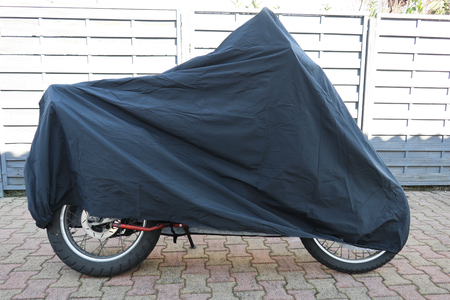 parked motorbike with protective cover in the street Standard-Bild