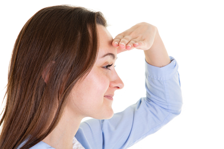 Young woman holding her hand at the forehead looking far away