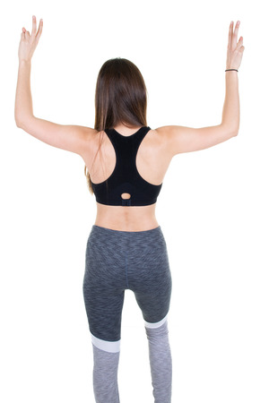 Rear view of a female athlete standing with hands arms up against white background Banco de Imagens
