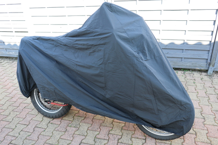 Protecting waterproof parking outdoors motorcycle cover jacket Stock Photo