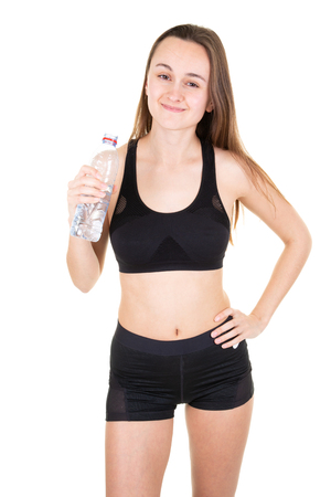 Young sport athletic woman wearing black clothes holding water bottle in gym Stock fotó