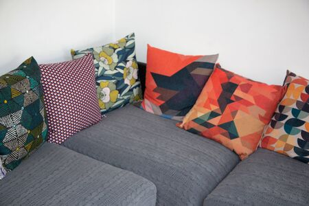 gray corner sofa with several colorful cushions in interior house Stok Fotoğraf