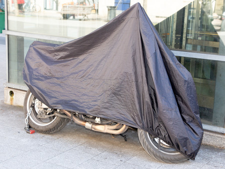 motorcycle in street protected by protective cover tarpaulin jacket