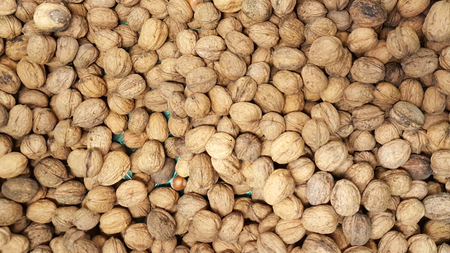 Top view background of walnuts in nutshells for sale market texture