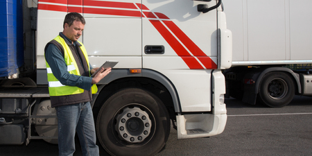 man driver with tablet computer in front of delivery logistics truck