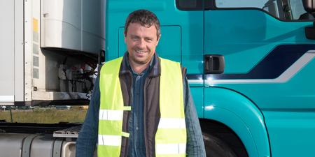 Hombre que conducía un camión posando conductor chico delante del camión Foto de archivo