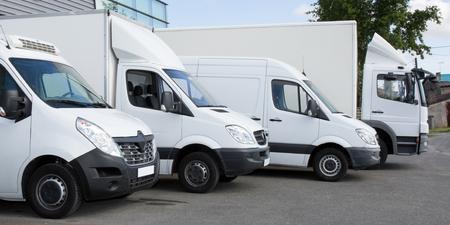 Servicio de entrega blanca van camiones coches en frente del almacén de la fábrica Foto de archivo
