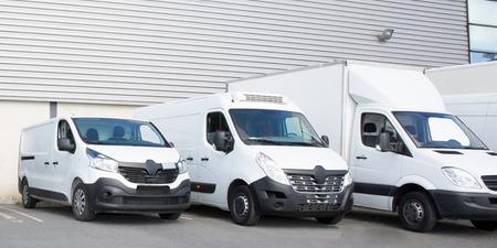 Estacionamiento especializado de la sociedad de entrega con varias camionetas blancas pequeñas
