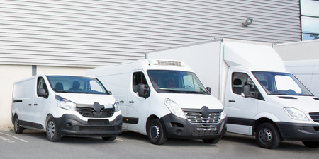 specialized delivery society parking with several white small trucks van Reklamní fotografie