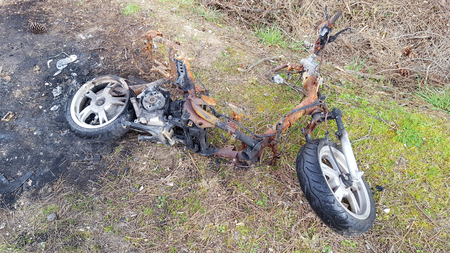 Burnt Out Motorbike scooter research by police Stock Photo
