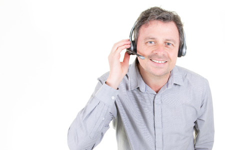 handsome young man in work in call-centre with headphones on white background with copy space