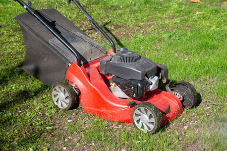 red lawn mower on green home garden Stock Photo