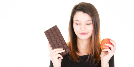 portrait of young pretty woman cute with apple and chocolate bar temptation