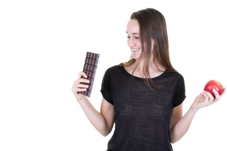 portrait of young woman with red apple in hand looking chocolate being tempted