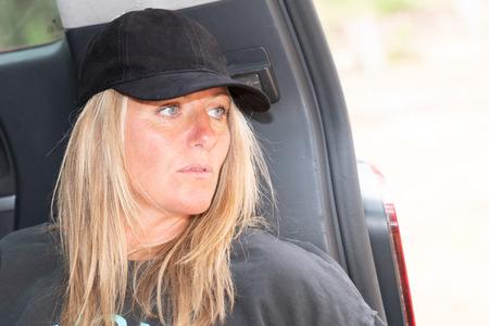 stylish pretty blond woman sitting on the rear van at beach posing travelling