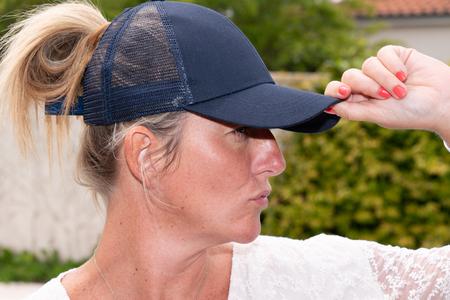Portrait of blonde woman wearing black baseball cap mockup template touch hat on head