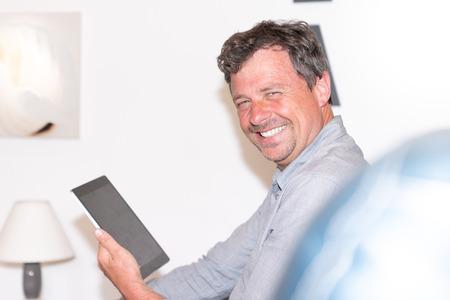 handsome man using tablet smiling at home 版權商用圖片