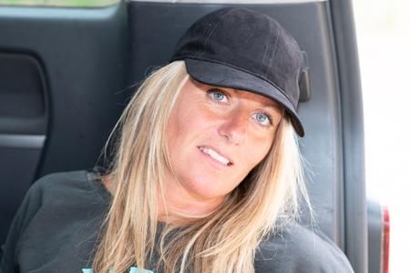pensive woman sitting alone outdoors in van car in summer