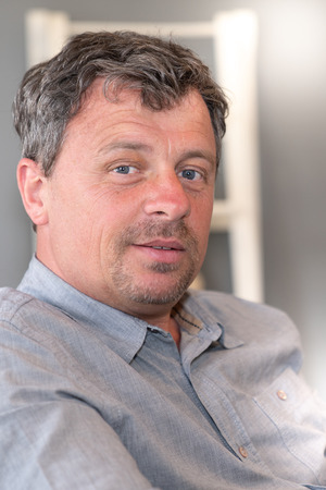 Portrait of middle aged man smiling at home Banco de Imagens