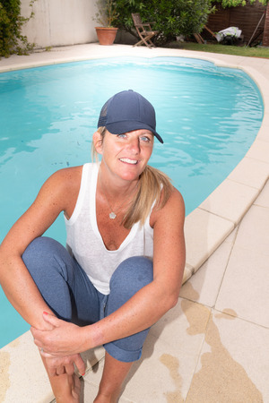 Portrait of blonde woman relaxing home swimming pool with cap