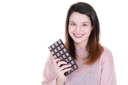 Portrait of pretty satisfied pretty girl ready to bit chocolate bar on white background aside blank copy space
