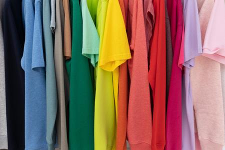 Regenbogenfarben Kleidung auf Kleiderbügeln für den Hintergrund