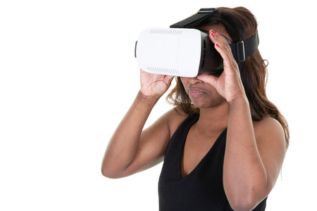 Studio shot of african american woman wearing virtual reality goggles watching movies playing video games