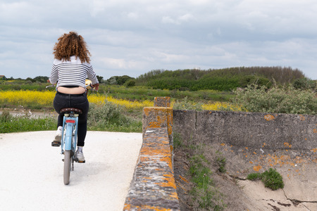 back view young woman cycling at seaside on island Ile de Re in west France