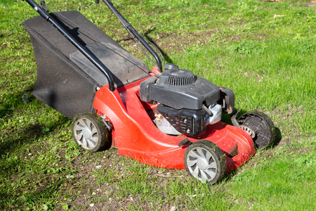 red lawn mower on grass spring cleaning care garden Imagens