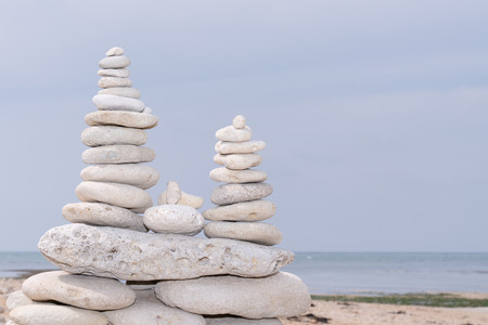 triple balance tower white grey pebble on a beach Imagens