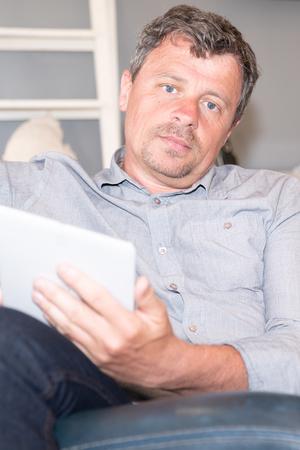 Handsome man at home relaxing in sofa with tablet