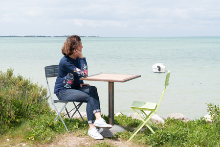 single woman relaxing on promenade with smartphone on seaside coast beach view