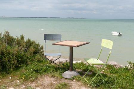 two chairs and metal table on seacoast summer in coffee restaurant empty with sea beach background Foto de archivo