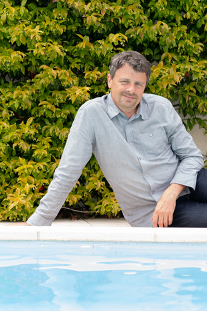 man in jeans sitting on edge floor by the swimming pool at home