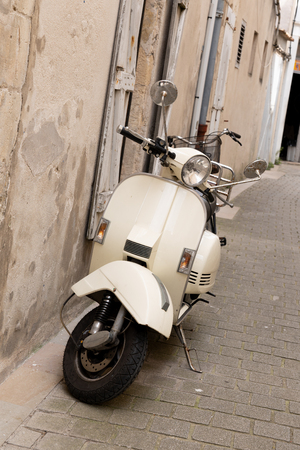 Italian streets city town and a popular single transport scooter parked by the wall in the empty street Foto de archivo