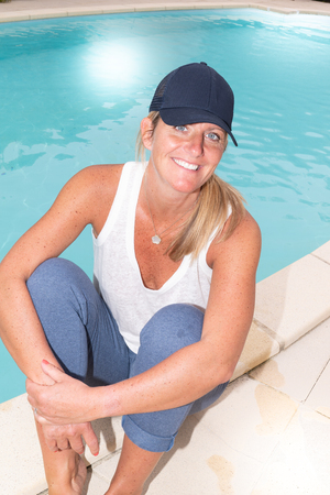woman in sport clothes relax sitting on edge floor by the swimming pool at home