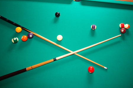green pool billiards table with balls and cue
