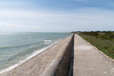 Grobla chroniąca wybrzeże i falochron na wyspie Ile de Ré we Francji ze ścieżką